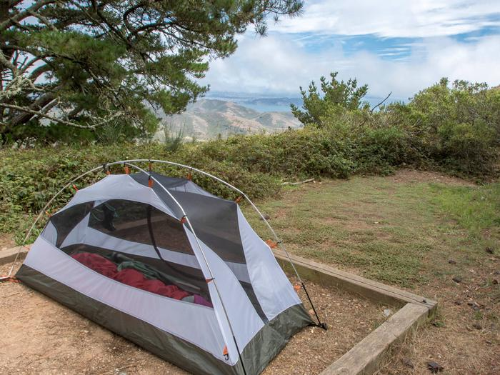 A tent in a tent pad at Hawk Campground, with a glimpse of the view in the background.A campsite with cypress trees in the distance.
