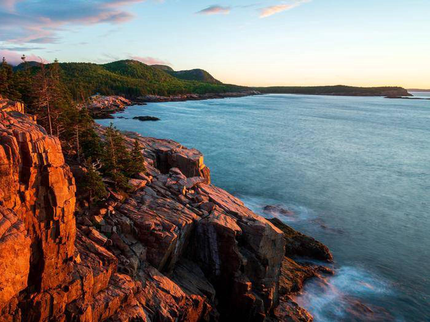 High, rocky coastline at sunrise with green mountains in distance and vast ocean belowSunrise at Otter Cliffs
