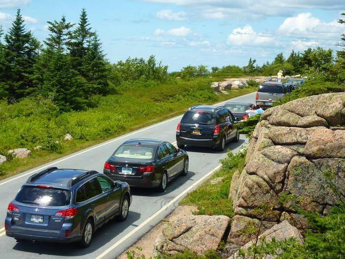 Row of passenger cars stopped in a two-lane road surrounded by trees and granite bouldersA line of traffic near the summit of Cadillac Mountain