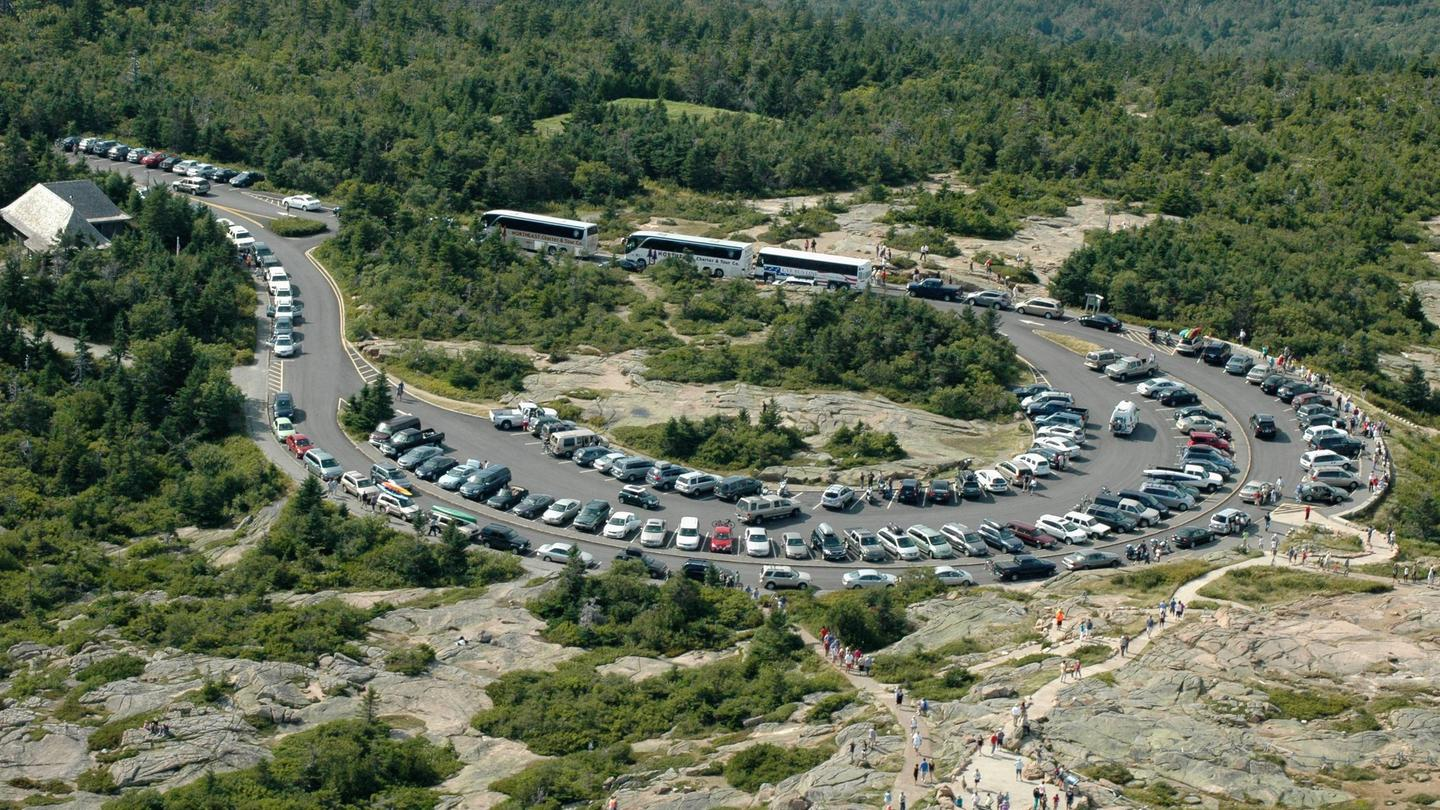 Rows of cars and buses fill a parking lot in a circular parking lot surrounded by trees and rocky surfacesAerial photo of limited parking at the summit of Cadillac Mountain