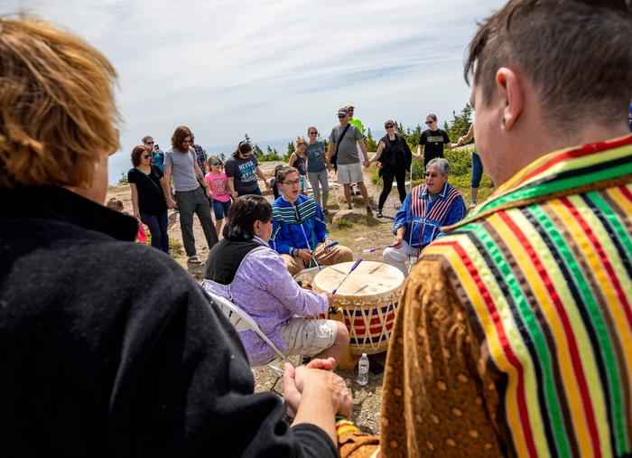"Three men sing while seated around a large drum surrounded by visitors in a circleBurnurwurbskek Singers, a men's drum group from the Penobscot Nation at Indian Island, Maine, perform traditional Wabanaki songs on the summit of Cadillac mountain as part of a ""Cultural Connections in the Park"" program"