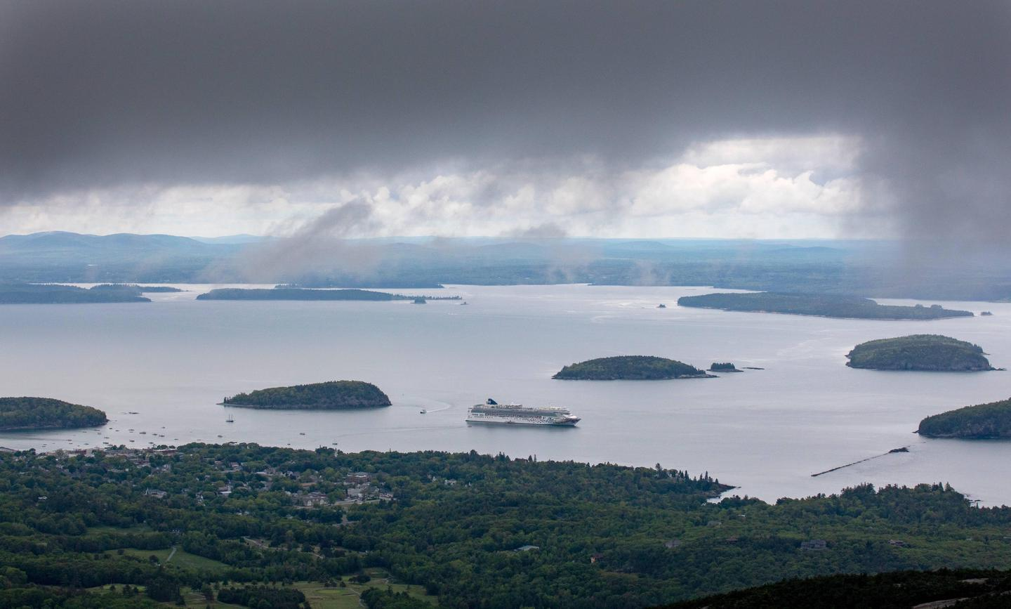Expansive view of a harbor with a cruise ship surrounded by small islands with dark clouds across the topView of Bar Harbor from Cadillac Mountain with dark clouds quickly descending