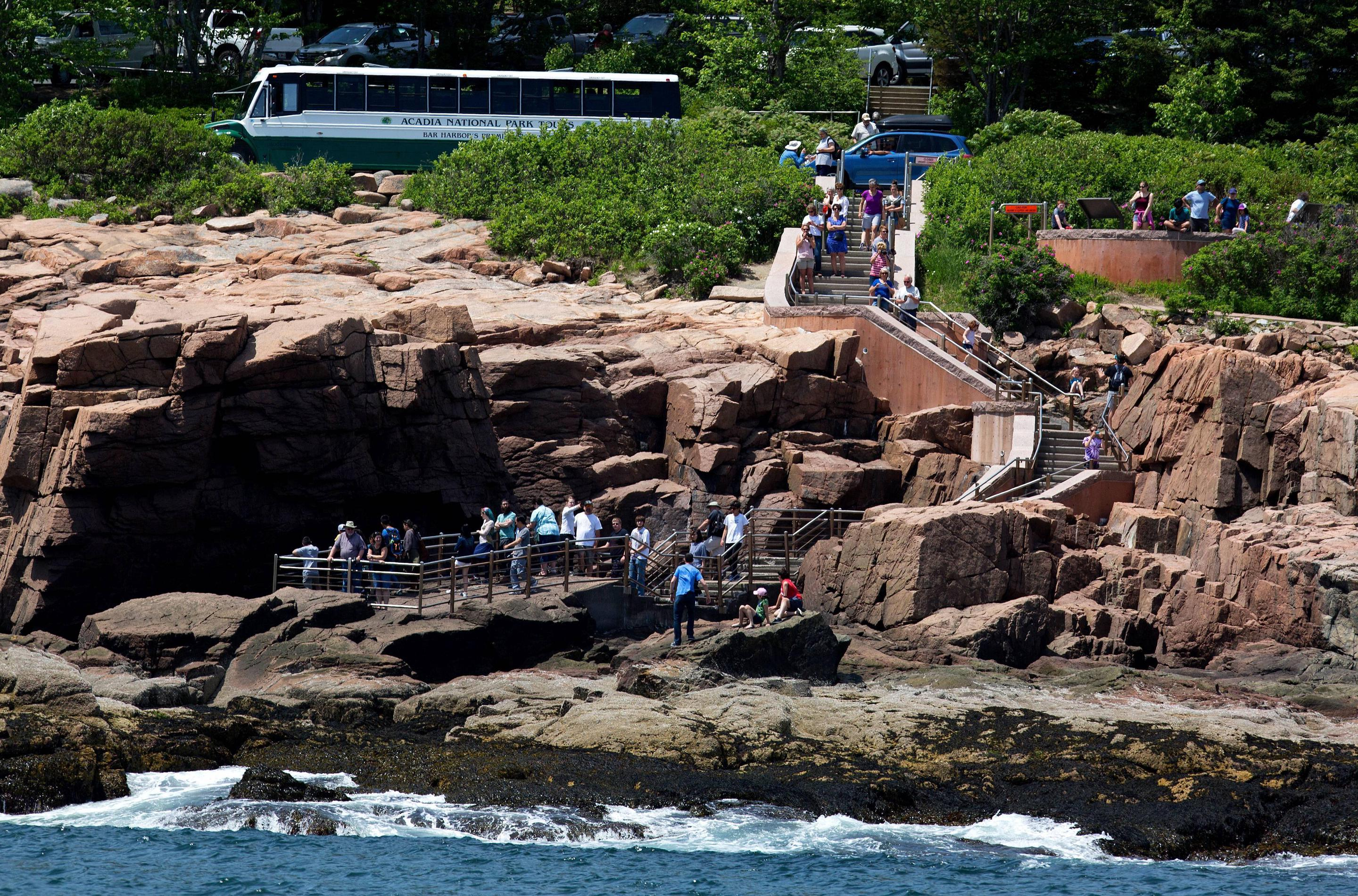 Along a rocky coastline, visitors crowd around railings and stone stairways from a busy road and parking area.Visitors clamber around railings at Thunder Hole.
