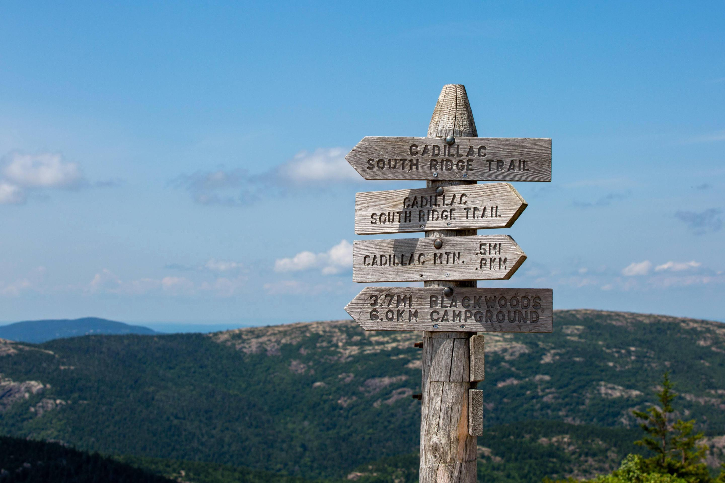Wood post on mountain top with four signs of trail names and distancesTrail sign post along Cadillac South Ridge Trail