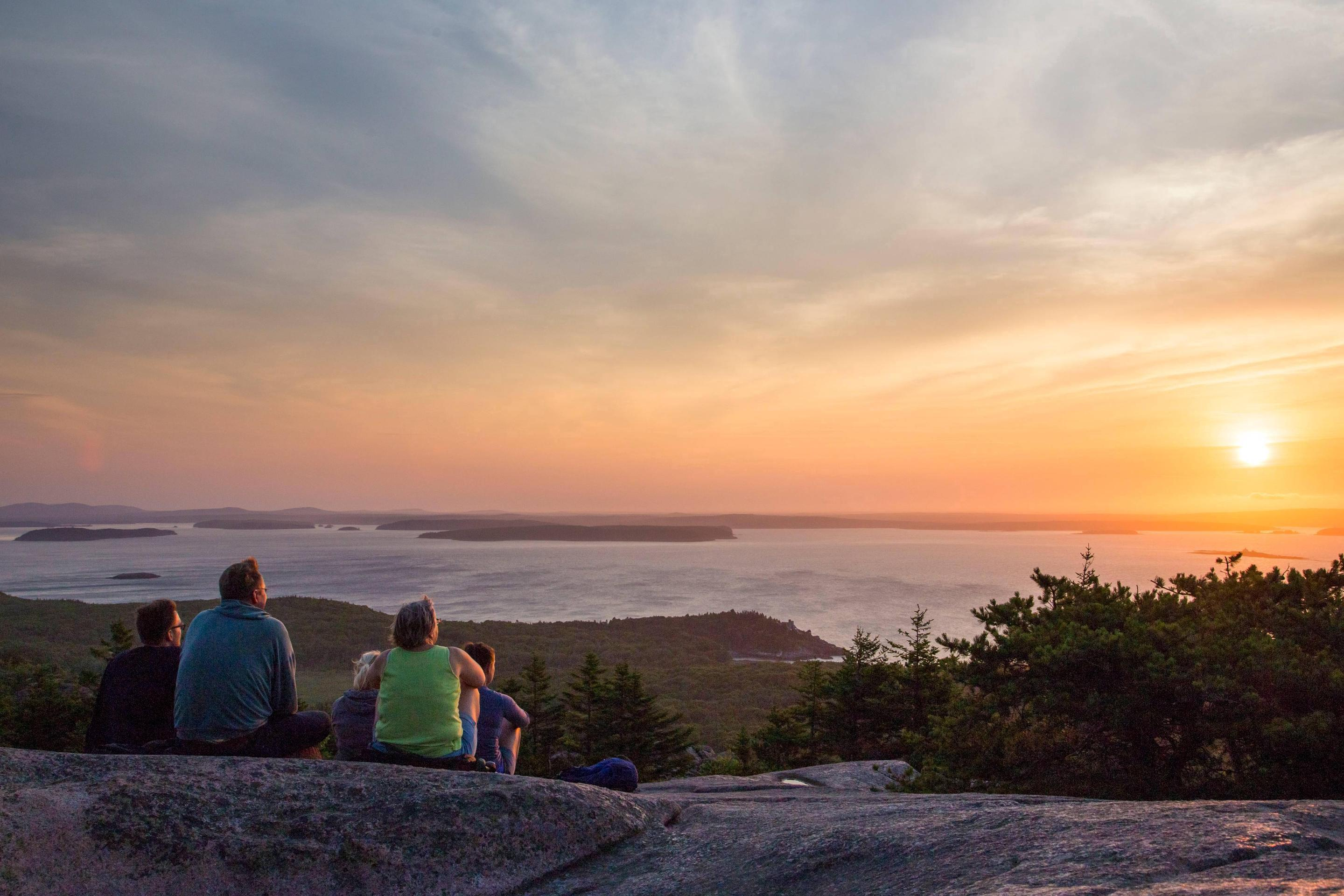 Group of people seated on rock mountain top watches sunrise in distanceSunrise on Cadillac Mountain