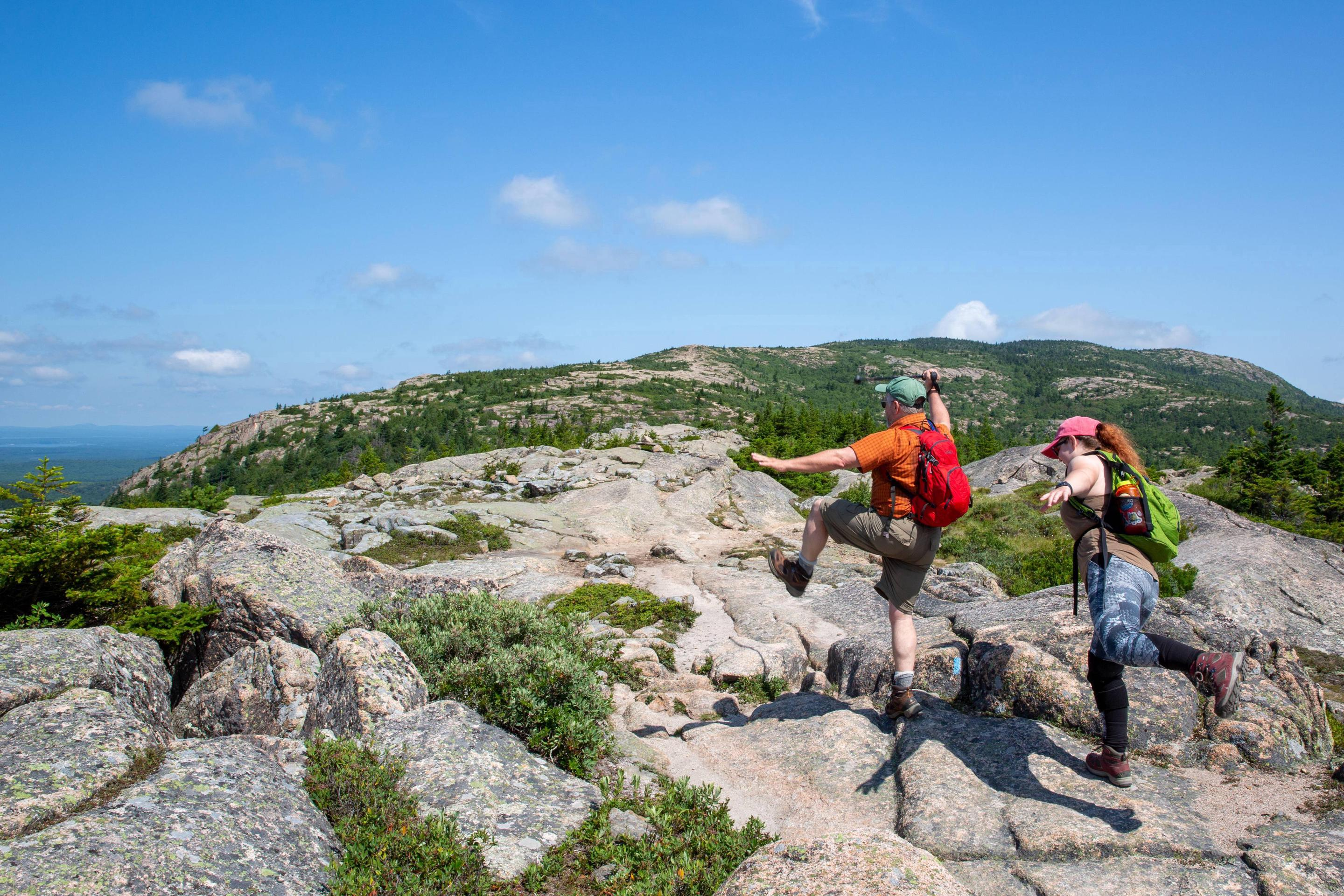 On an expansive rocky mountain top, two hikers wearing packs, boots, and ball caps gesture dramaticallyFather and daughter hikers clown along the Cadillac South Ridge Trail