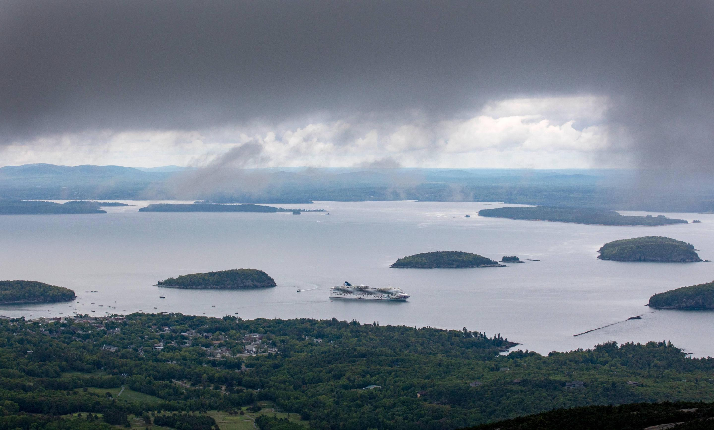 Expansive view of a harbor with a cruise ship surrounded by small islands and a dark band of clouds along topView of Bar Harbor from Cadillac Mountain with dark clouds quickly descending.