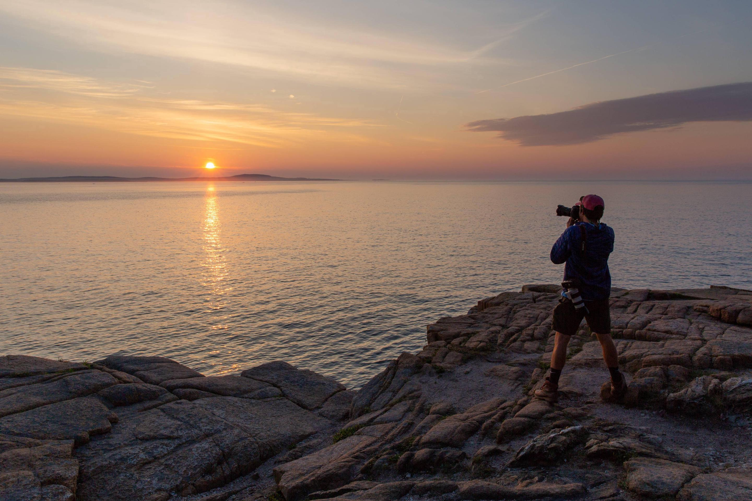 Man standing on rocky coastline takes a photo of sunrise Sunrise at Otter Cliffs