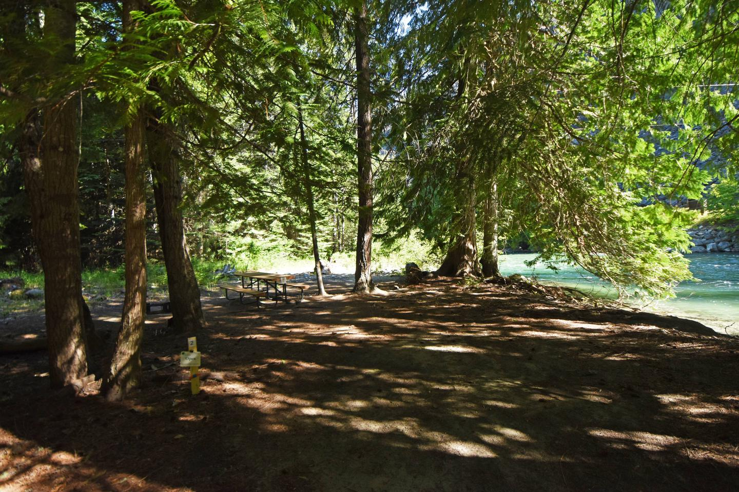 View of campsite next to river with picnic table and tent pads.View of Harlequin Campsite 2