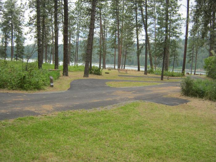 Pine forest in backgroundPull Through Paved Parking of Site 5, Trees and lake in background