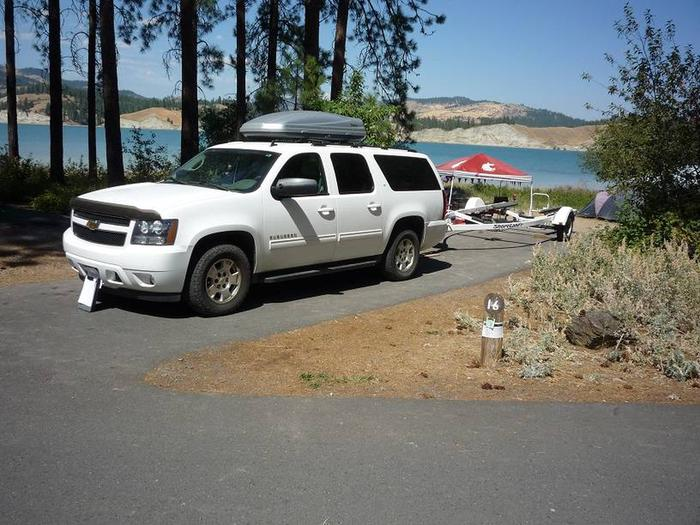 Site #16 Back in site, paved with trees and lake in the background.Site #16 tip out either side.