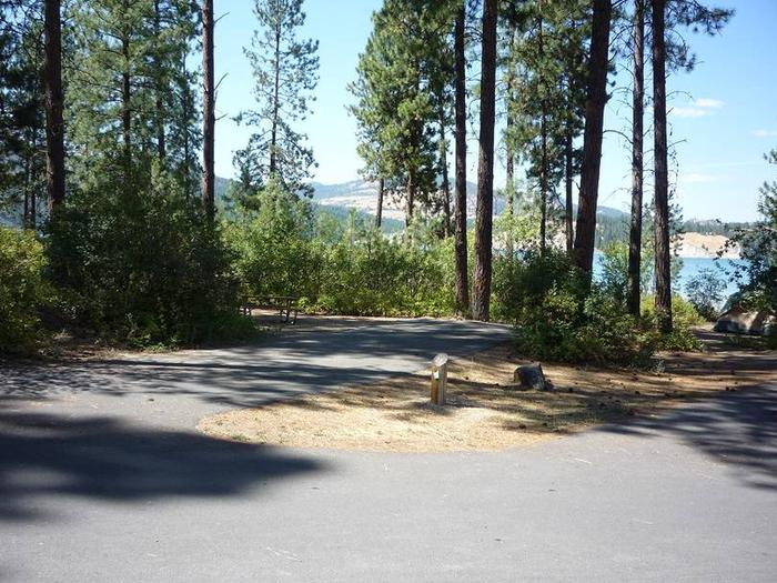 Site #21 Back in site, paved and surrounded by bushes with trees and lake in the background.Site #21 tip out either side. Caution trees at end of asphalt.