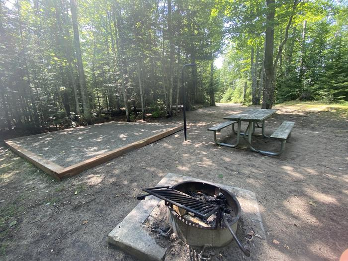 Tent pad, picnic table, fire ring and lantern pole.