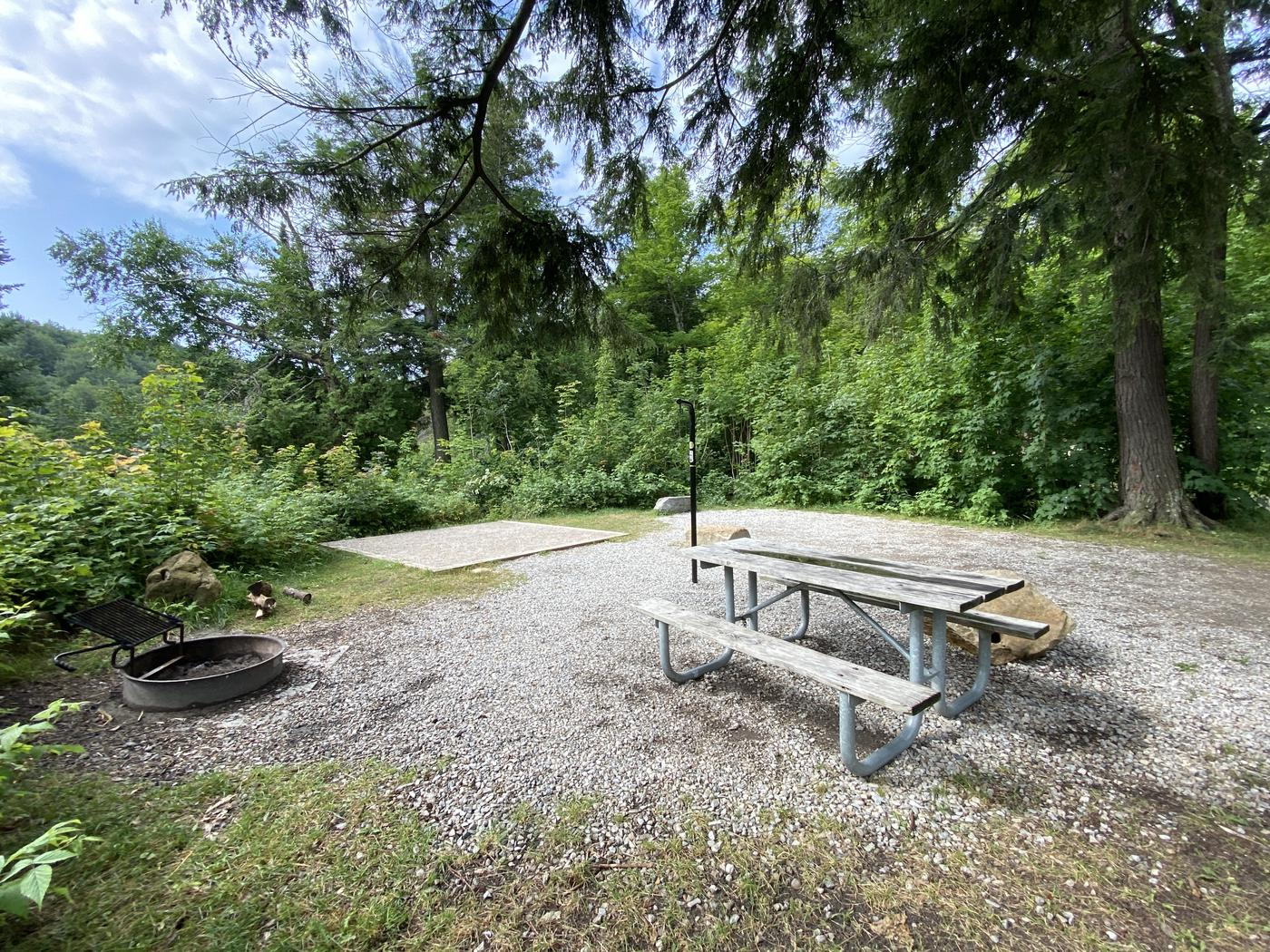 Fire ring, picnic table, lantern pole and tent pad.