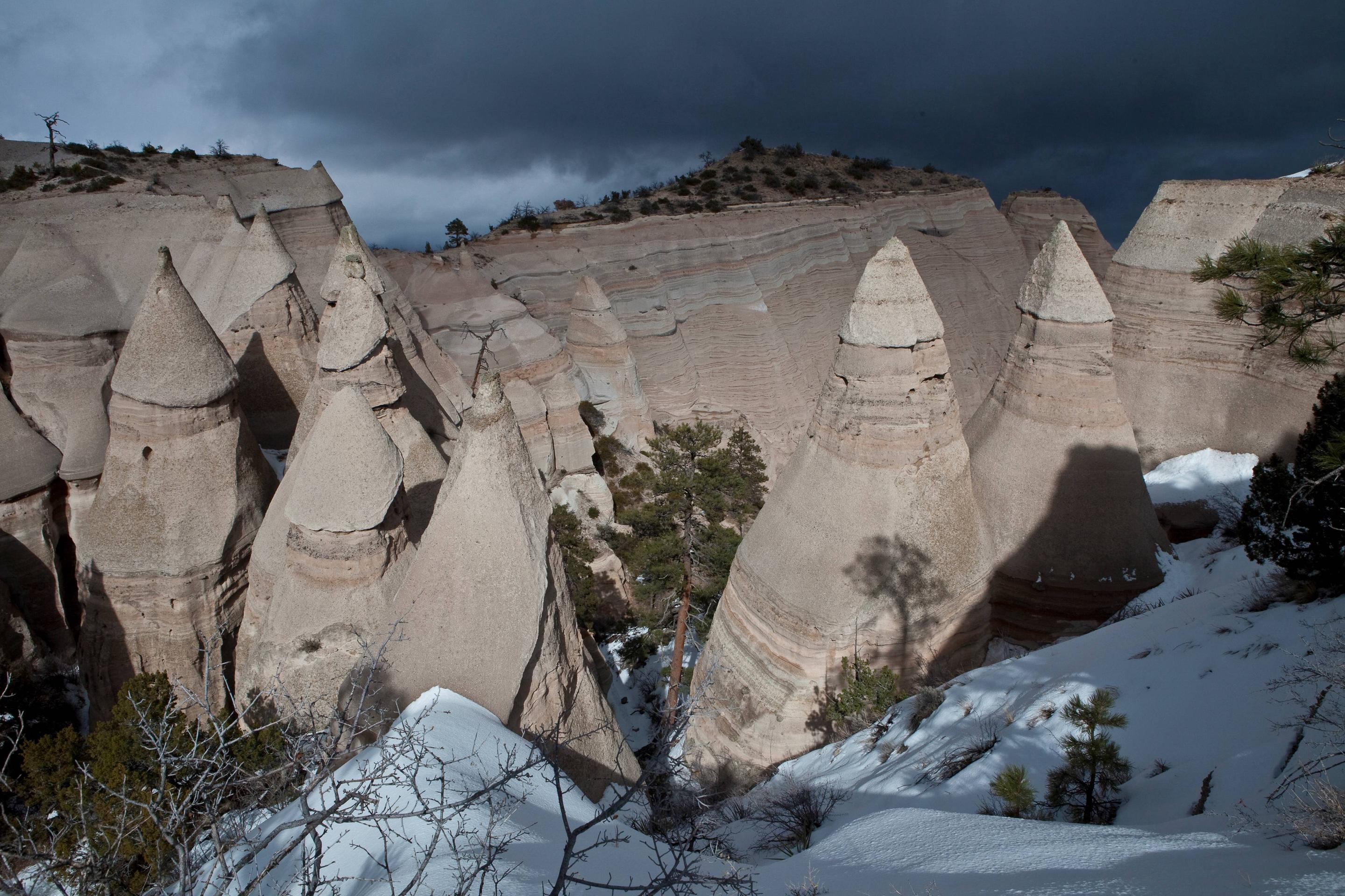 Snow at the base of tent rock formations