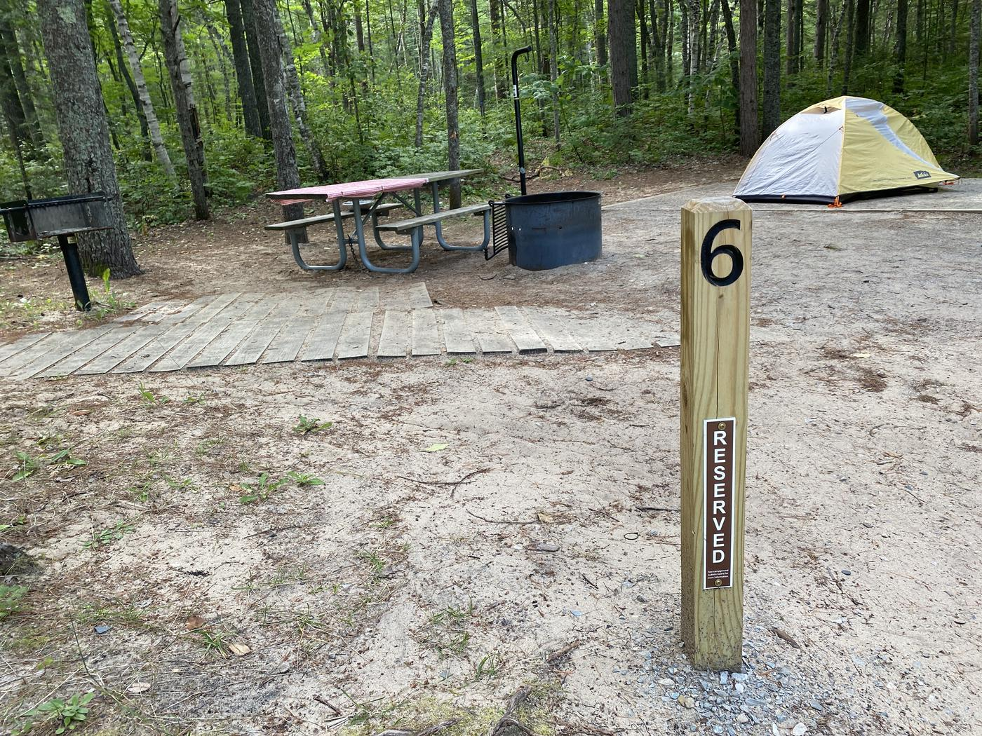 Tent pad, accessible picnic table and fire ring, lantern pole.