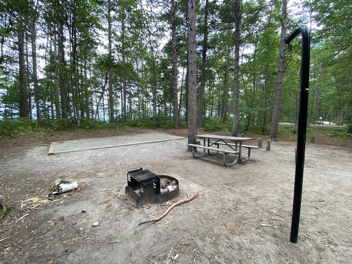 Lantern pole, fire ring, picnic table and tent pad.