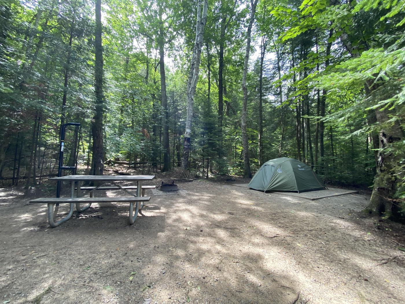 Tent pad, picnic table, fire ring and tent pole
