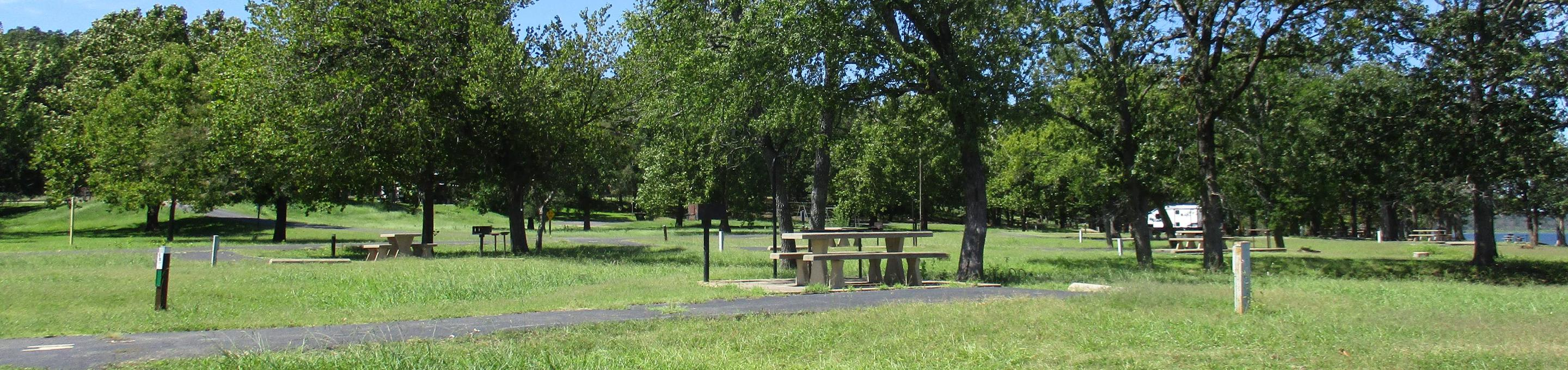 Site 14 - WildwoodSite 14 is a back-in site surrounded by a large green space.  Site offers minimal shade at picnic table.
