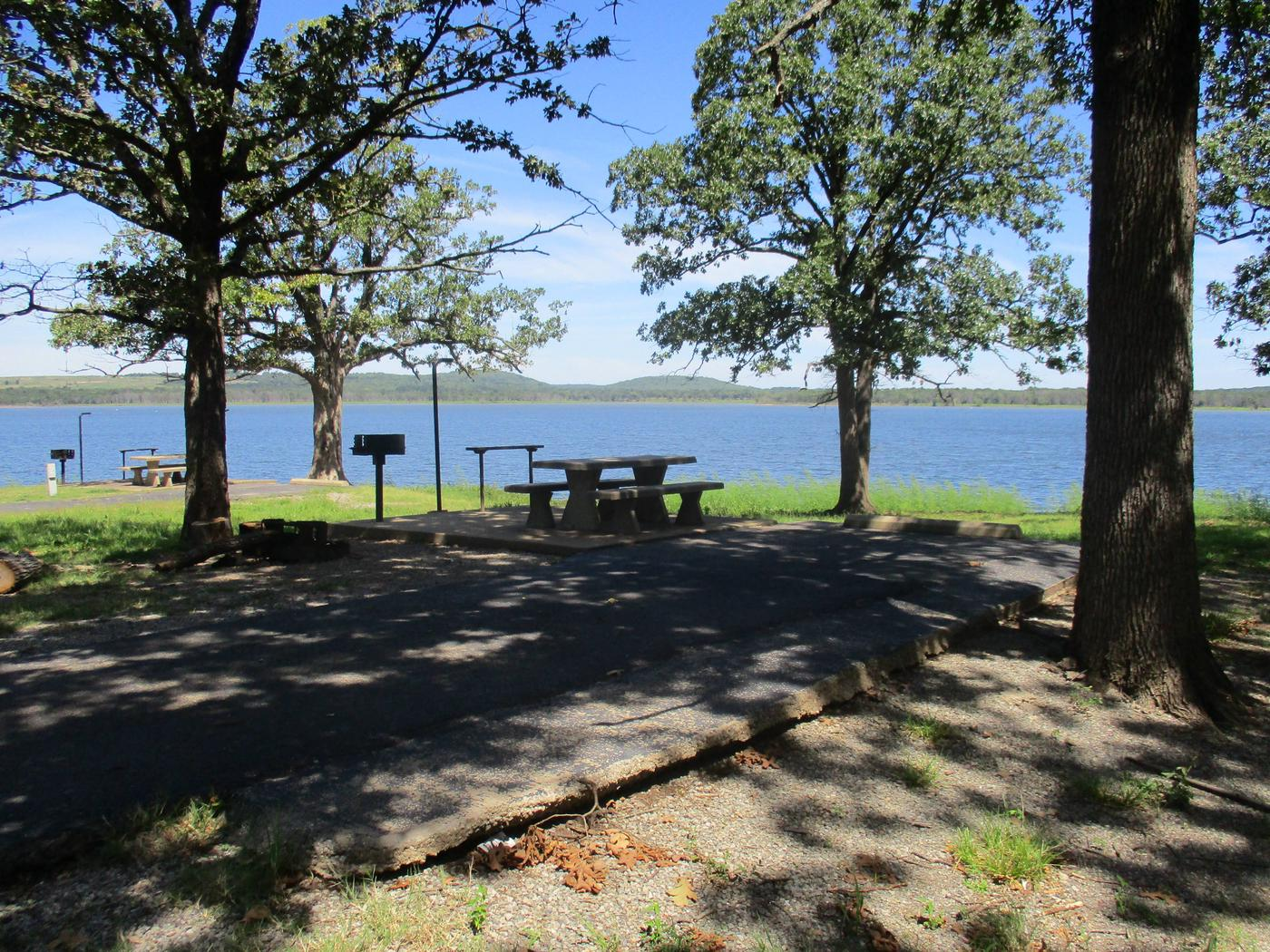Wildwood - Site 23Site 23 offers a concrete picnic table, pedestal grill, utility table, lantern holder and fire ring.