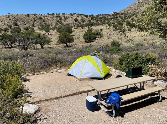 Tent site number seven, displaying a two-person tent on tent pad and view of hillside in background.