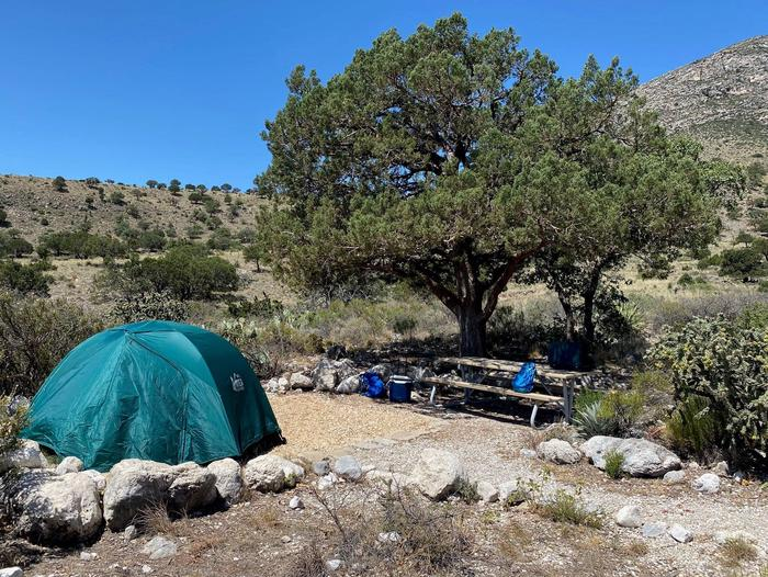 Tent campsite number 8, displaying two-plus person tent on tent pad with view of hills in background.Tent campsite number 8, displaying two-plus person tent on tent pad.