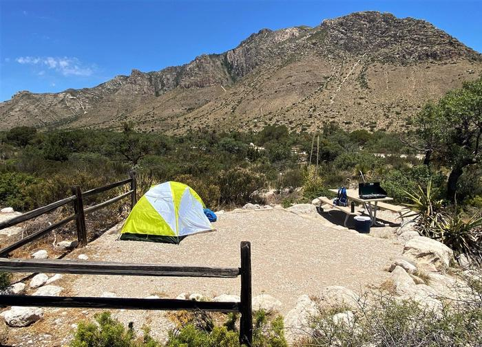 Pine Springs campground tent site.  The tent pad and picnic table are is delineated by larger rocks and fencing.  The surface is covered with find gravel. A view of Hunter Peak is in the background.Pine Springs campsite with views of Hunter Peak in the background.