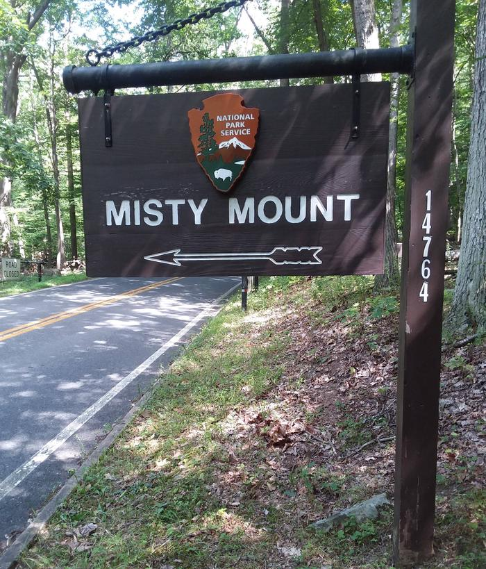 Outdoor wooden sign on road with NPS Arrowhead. Sign labeled Misty Mount with an arrow symbol.Camp Misty Mount entrance sign, located .7 mile from the Visitor's Center on Park Central Road.