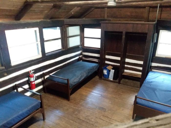 Interior of American chestnut log cabin.  Wooden floor, 3 metal cots with vinyl covered mattresses.Interior of American chestnut log cabin.  Cabins have interior and exterior lighting, metal cots with vinyl covered mattresses, waste and recycle receptacles, and brooms.