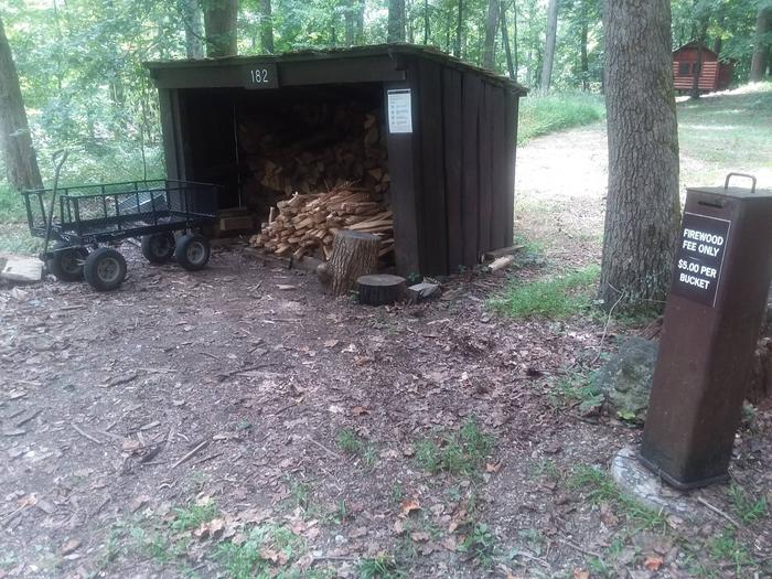 Three sided wooden shed filled with firewood. A metal fee collection box and metal wagon are next to the shed.Camp Misty Mount has two firewood sheds. Firewood is available for a small donation. Firewood brought in from areas outside the park is prohibited.