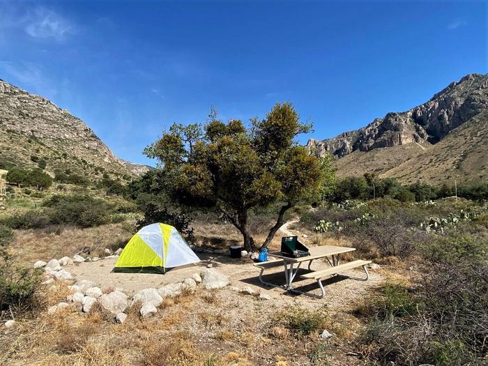 Tent campsite number one, with views of the mountain range and displaying a 2-person tent on the tent pad.
