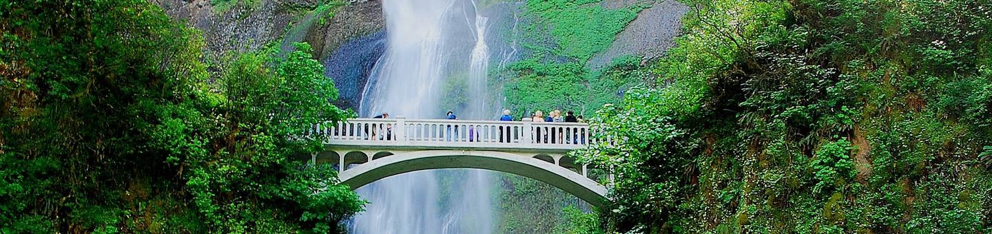 Multnomah Falls along the Historic Columbia Falls RiverVisitors standing on a bridge at Multnomah Falls overlooking a waterfall