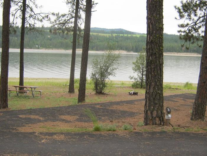 Back in site, paved with trees and lake in the background.Site #3 Back in site, paved with trees and lake in the background.