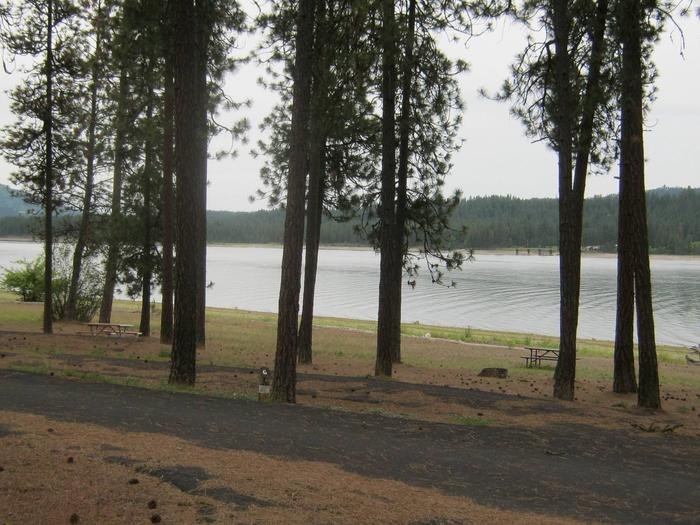 Site # 6 Pull through site, paved with trees and lake in the background.Site # 6