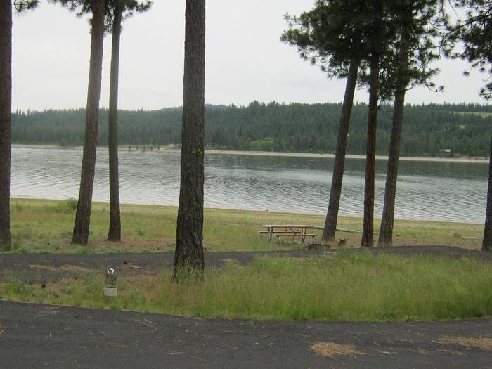 Site #12 Back in site, paved with trees and lake in the background.Site # 12