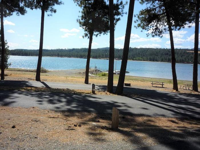 Site #21 Pull through site, paved with trees and lake in the background.Site #21
