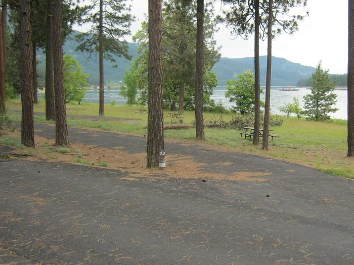 Site #22 Pull through  site, paved with trees and lake in the background.Site #22