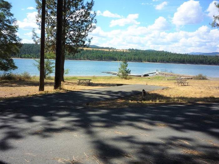 Site #25 Back in site, paved with trees and lake in the background.Site #25