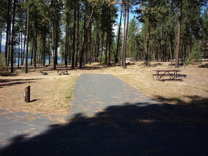 Site #33 Back in site, paved with trees and lake in the background.Site #33