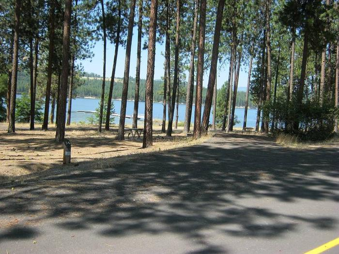Site #34 Back in site, paved with trees and lake in the background.Site #34