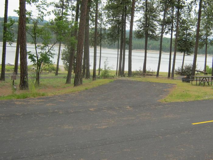 Site #36 Accessible back in site, paved with trees and lake in the background.Site #36