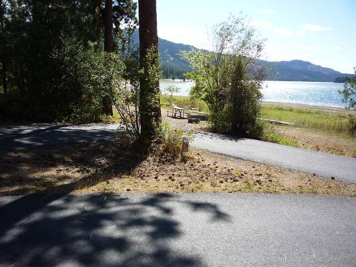 Site #40 Pull through site, paved with trees and lake in the background.Site #40