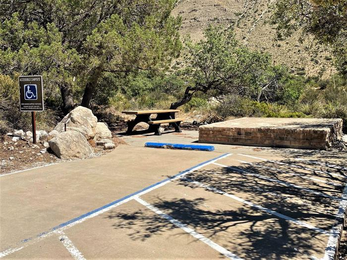 Accessible tent campsite #17 with raised tent pad, picnic table and concrete surface with desert vegetation and trees on each side.Accessible tent campsite #17 with raised tent pad. This site offers an accessible parking space.