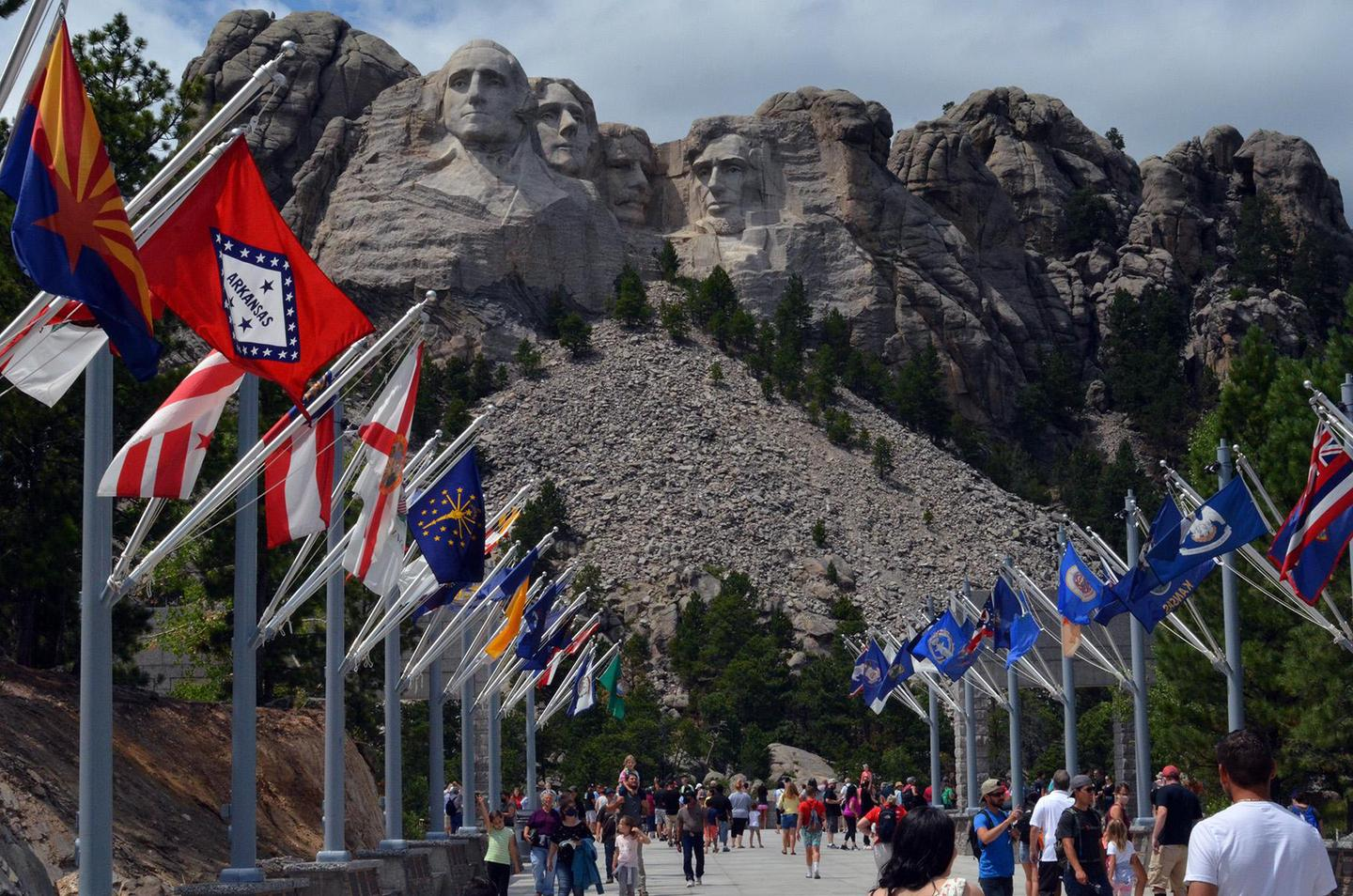 Mount Rushmore and the Avenue of FlagsVisitors walking along the Avenue of Flags with Mount Rushmore in the background.