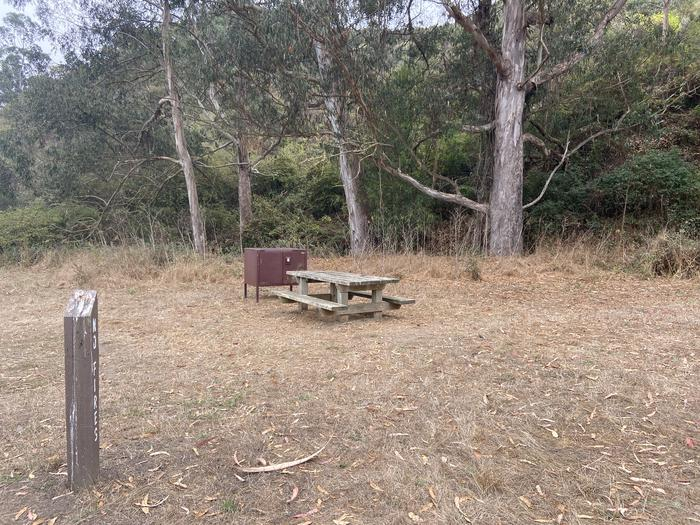 Campsite 1 with a sign post, picnic table, and food locker.Campsite 1