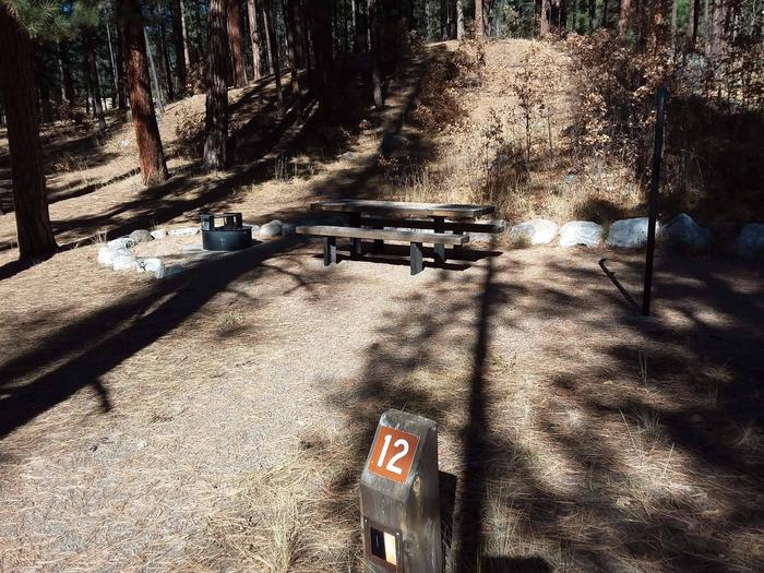 Campground 12 is situated at a small hill with a table, fire ring, and a lantern post.Site 12