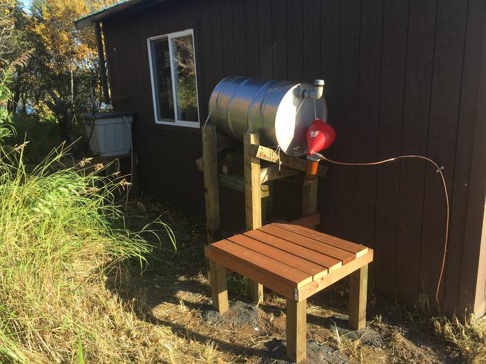 55 gallon fuel drum for oil stove. Rain barrel can be seen at rear of cabin