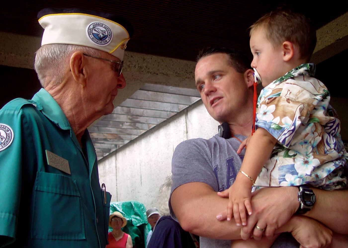 Two visitors talking to WWII veteranPearl Harbor Survivor Everett Hyland (USS Pennsylvania) passes his story onto another generation.