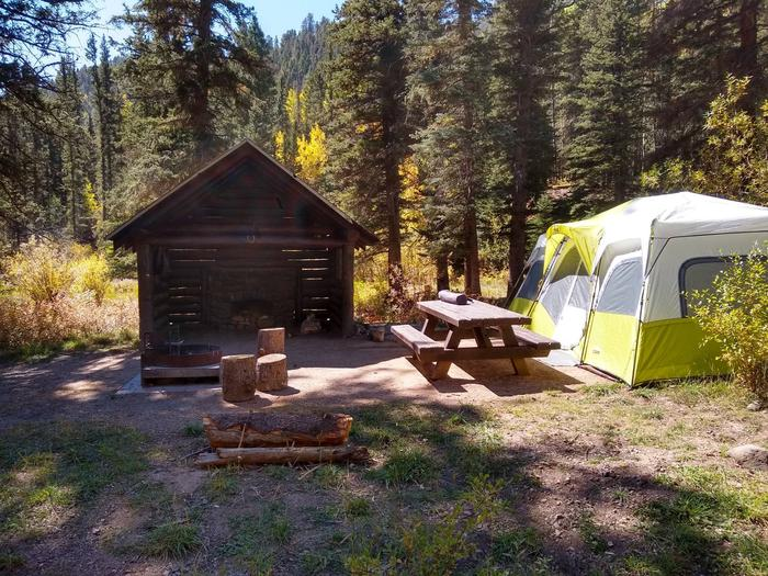 A sheltered unit in the shade with a fire place, picnic table, fire ring and a green and white tent to the side.Panchuela Site 6