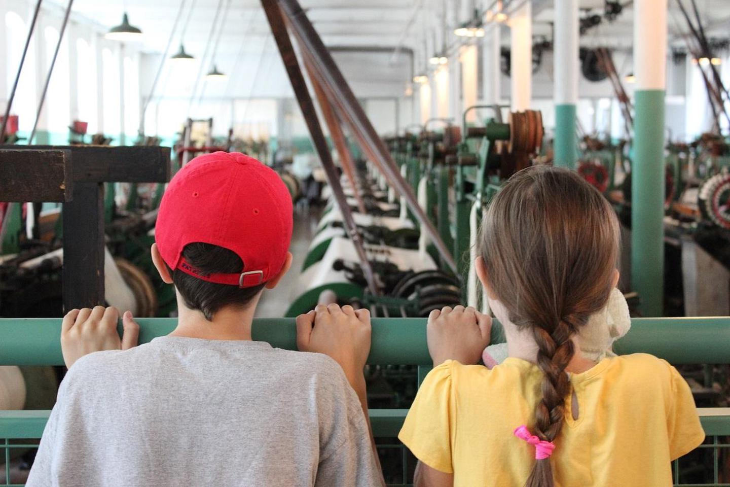Two children explore the weave room at the Boott Cotton Mills Museum